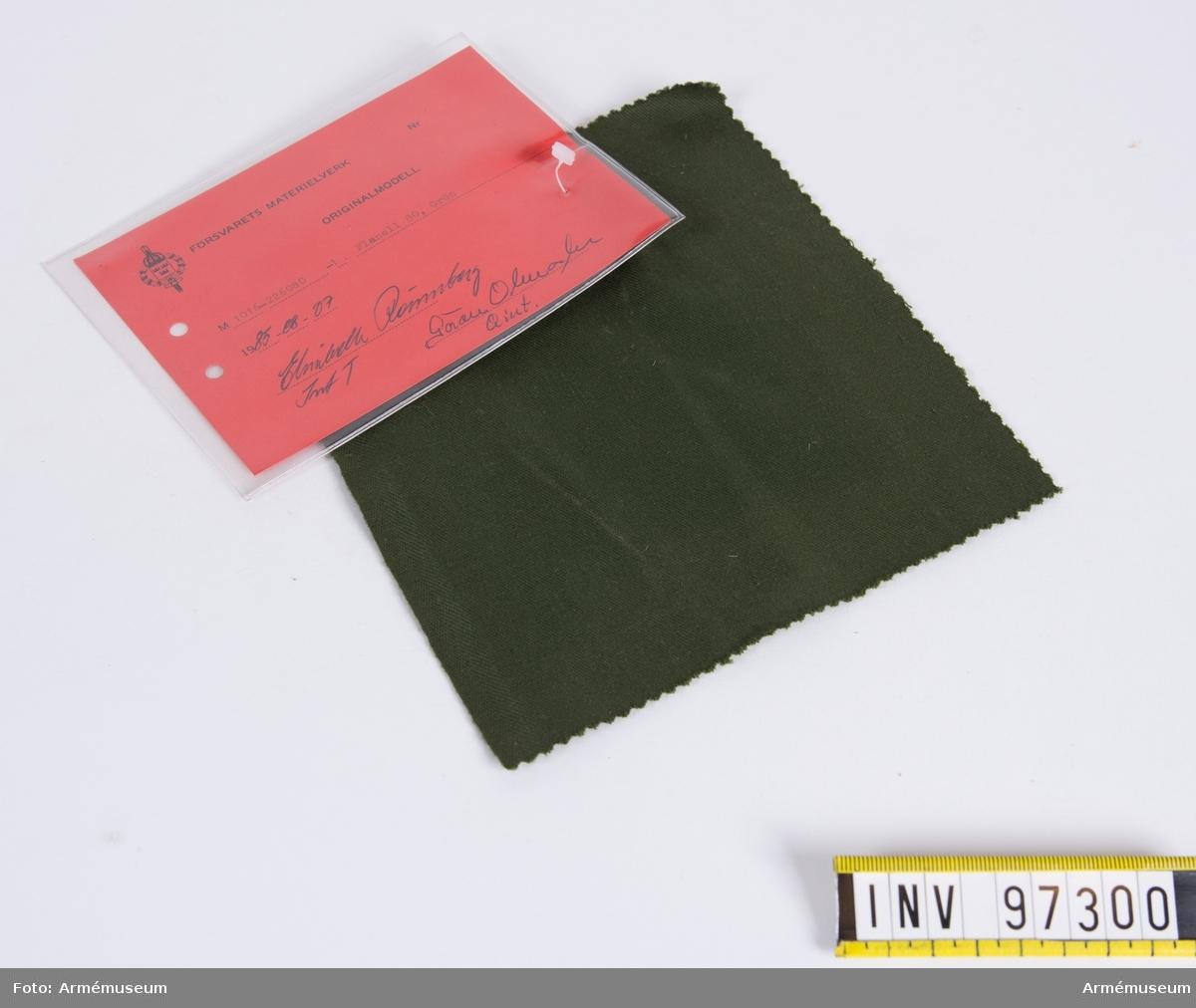 """Vidhängande modellapp med text: """"Försvarets materielverk. Originalmodell. M 1016-226080-1. Flanell 80, Grön. 1985-08-07. Elisabeth Rönnberg IntT, Göran Olmarker QInt."""""""