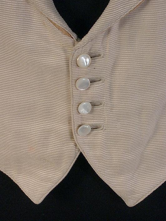 Ljus, nästan vit (lila), enkelknäppt, fyra pärlemorknappar, pikétyg (osäker uppgift) vitt foder.