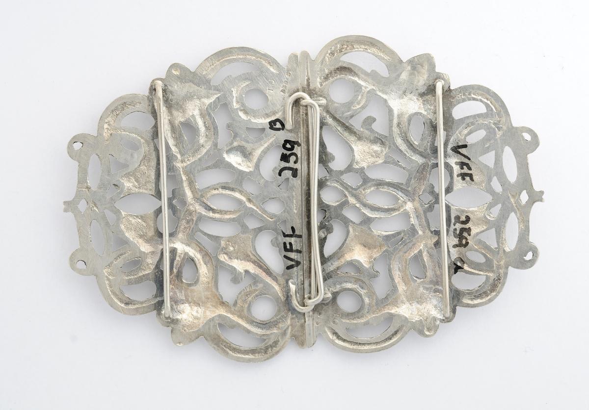 Beltespenne, A og B, støypt i sølv. Gjennombrote ranke og slagemønster som dekor. På baksida to hemper tvers over, ei på kvar del, for å hekte dei saman med. Stempel på baksida med TO 830 S