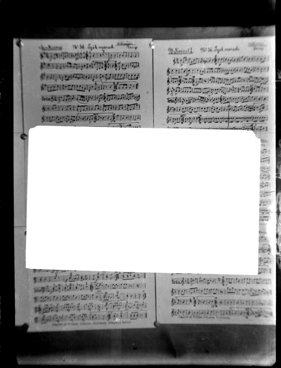 Bilde av noter til bl.a tysk marsj fra ca 1910 - 1920. Et hvitt ark foran notene.