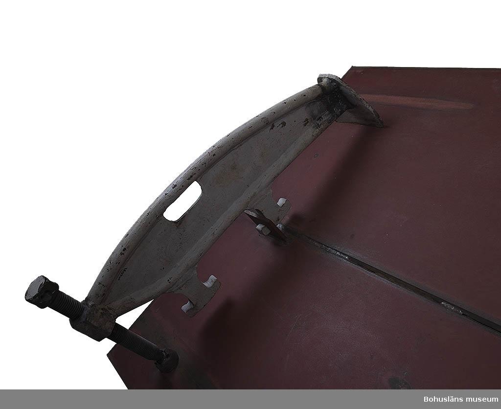 """Jacklamsen sitter fastspänd på sektionsmodell UM020117.  Utställningstext till fotografi föreställande svetsning vid Uddevallavarvet; """"Innan det gick att svetsa ihop plåtbitarna så skulle plåtslagarna se till att plåtbitarna passade ihop. Därefter svetsade grovplåtslagarna ihop plåtarna innan den riktiga svetsningen. Under arbetets gång hölls plåtarna fast med jacklams""""."""