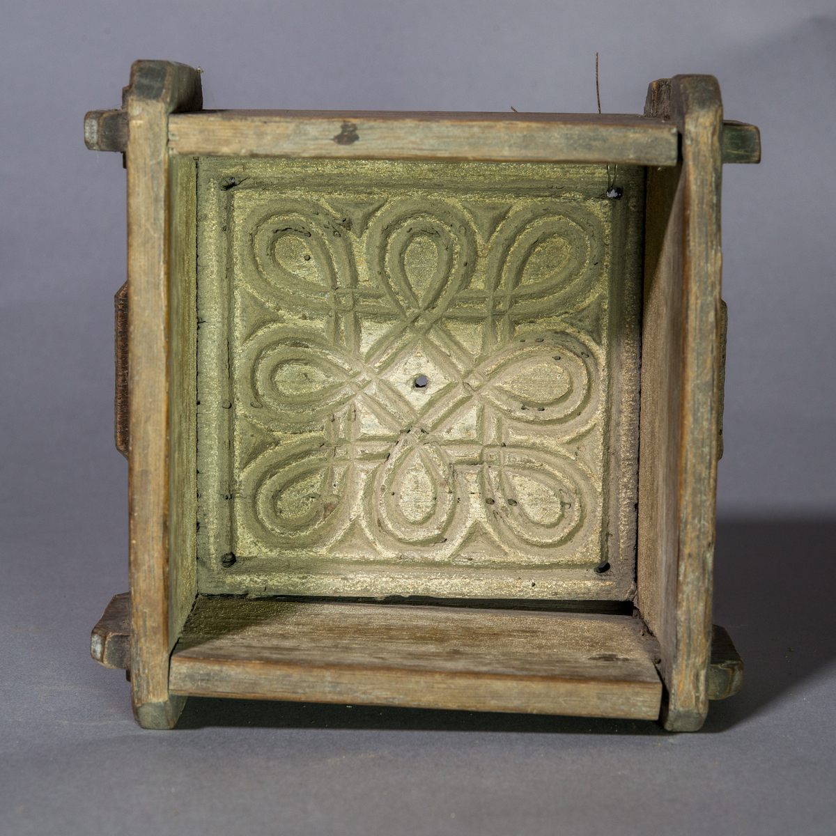 Ostkar av ek, kvadratiskt och öppningsbart. Botten med dekorativt utskuret mönster i form av två stycken omlott liggande Sankthanskors.
