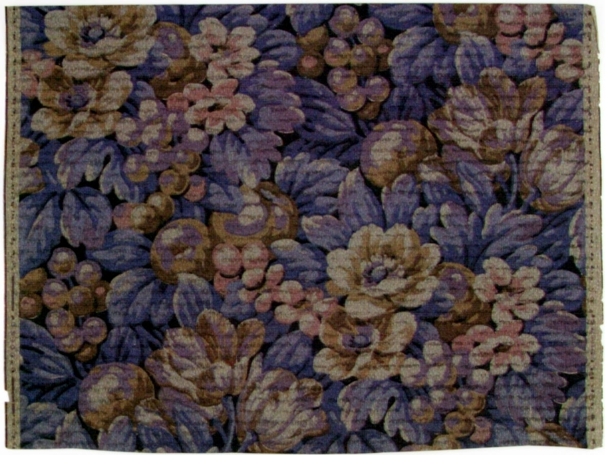Tätt ytfyllande blommönster i flera bruna, blå och ljuslila nyanser på ett grått genomfärgat papper. Övertryck med streckmönster.