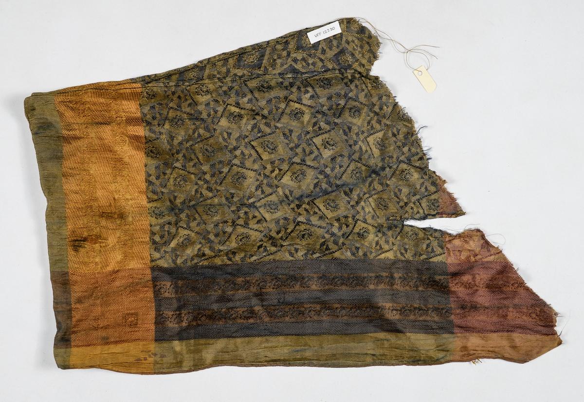Sjerf i silkedamask i svart, gult, grønt. Jarekant i eine sida, falda i den andre.  Samansydd på midten.