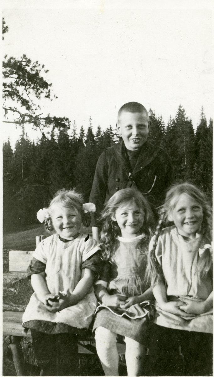 3 blide småjenter sitter på en benk. En like blid gutt står bak dem.