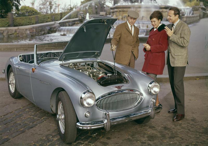 Reklamefoto fra Tiedemanns Tobaksfabrik. Tre modeller røyker sigarett ved siden av sportsbil.