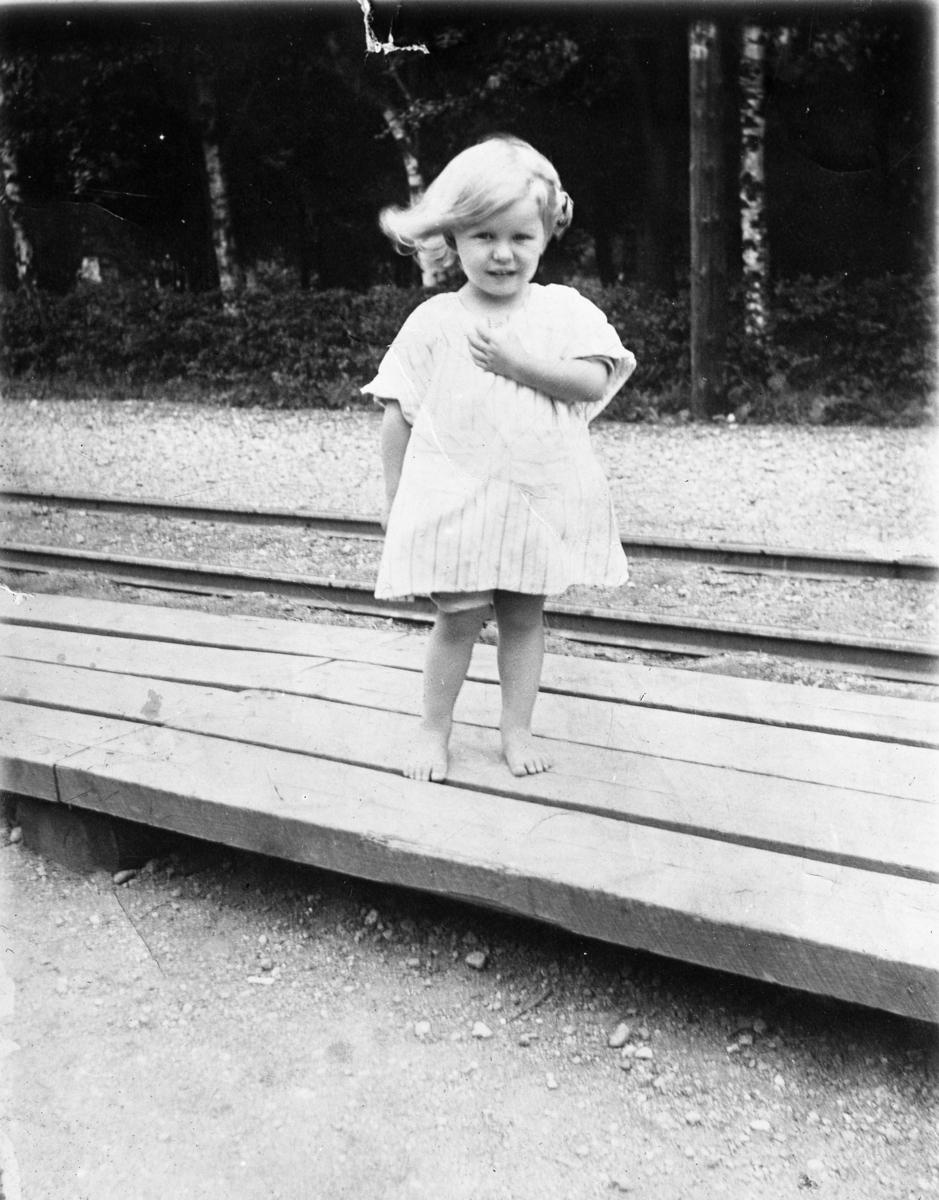 Reprofotografi av liten flicka med vind i håret vid järnvägsstation.