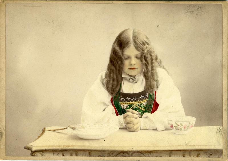 Kolorert studiofotografi av jente med Hardangerdrakt, sitter med foldelde hender på bord. 1903. (Foto/Photo)