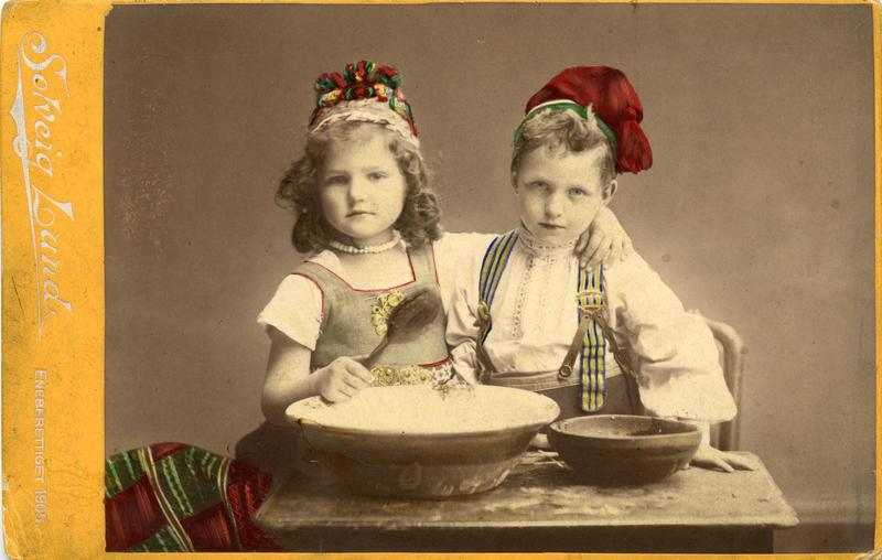 Kolorert studiofotografi av jente og gutt med drakt, sittende ved bord med to treboller, ei sleiv. 1905 (Foto/Photo)