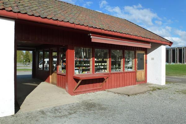 Museumsbutikken er et tødt, lavt hus ved hovedinngangen.. Foto/Photo