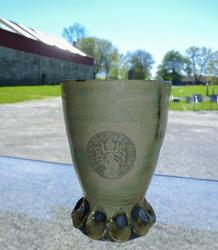 """Hånddreid keramikkrus produsert på bestilling fra museet. Krusene er grønnglasserte og har """"logoen"""" til den siste katolske biskopen på Hamar som merke i glasseringa."""