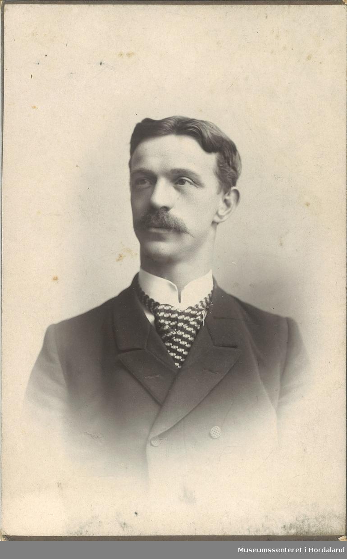 portrettfotografi av ung mann med bart, mørk jakke, kvit skjorte med stivesnipp og stort mønstra slips