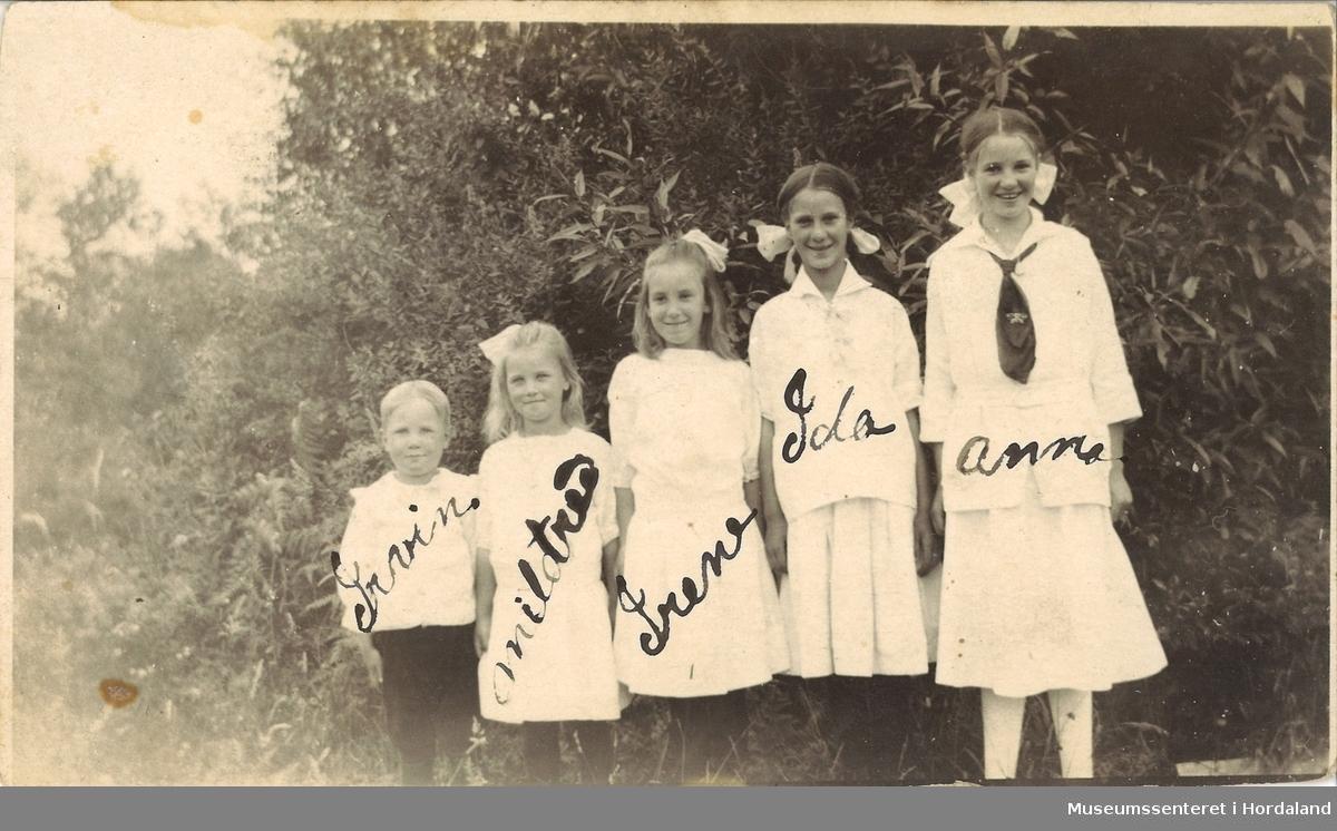 amatørfotografi av fire jenter og ein gut kledd i kvite klær som står på rad framfor busker
