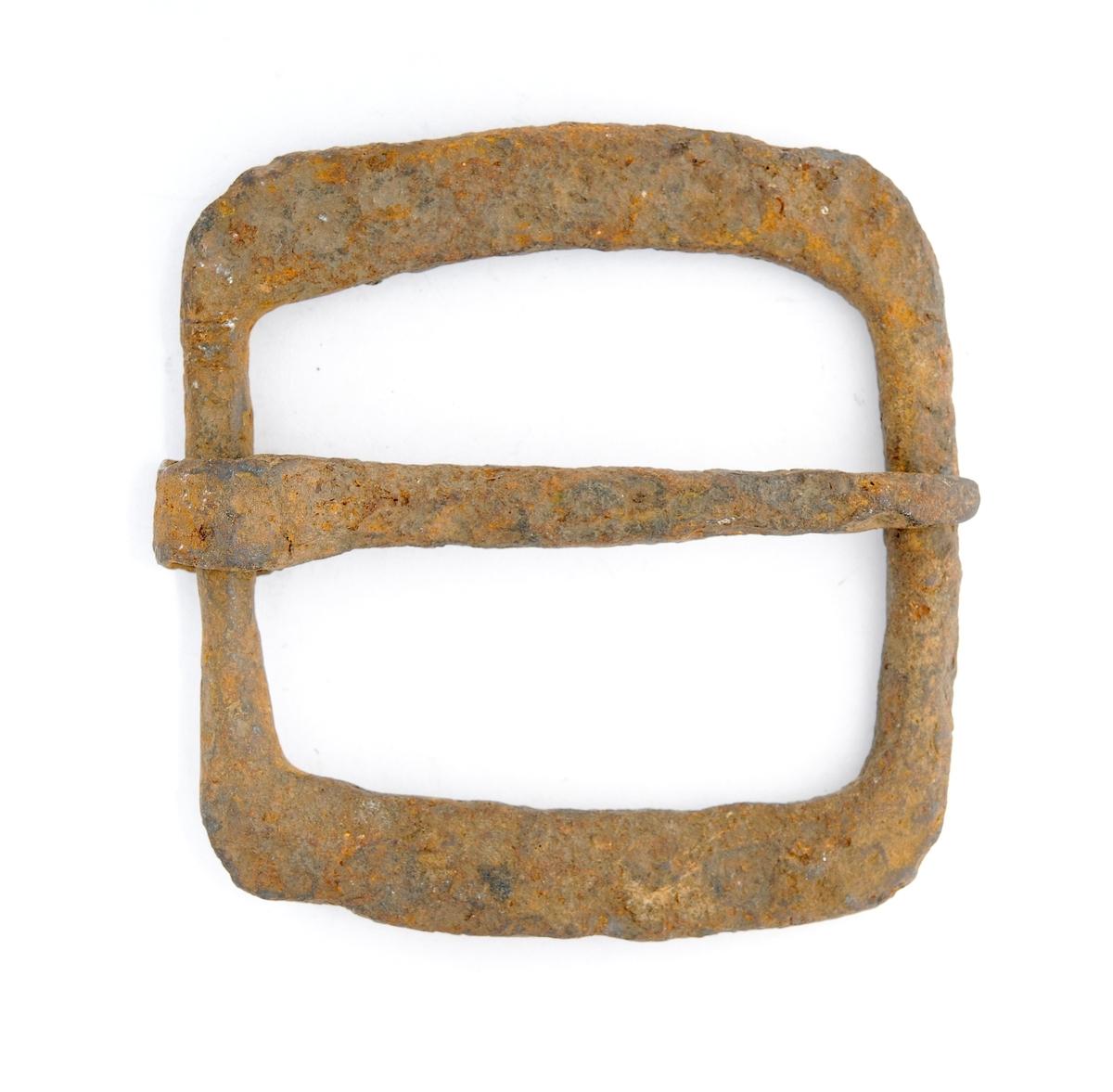 Spenne i støypt jern. Til hestesal? Rektanguler flat form. Tann smidd rundt stolpen. Ingen dekor. Litt rusta.