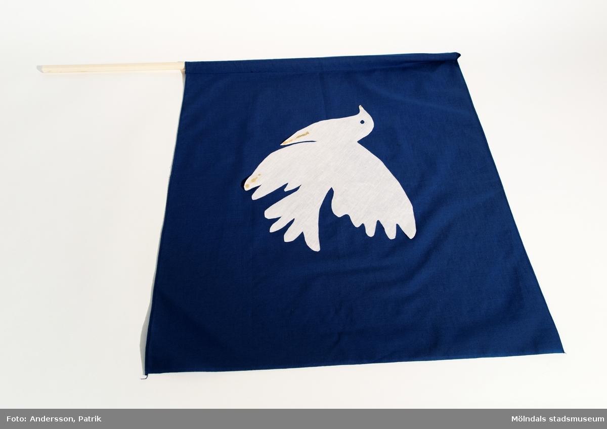 Flagga som användes i fredsmarschen, troligtvis 1984. Marschen gick från Rävekärr till Lindome kyrka och avslutades med gudstjänst i Lindome kyrka.  Flaggan är blå ich har en vit fredsduva i mitten. Pinnen som man håller i, är av plast.