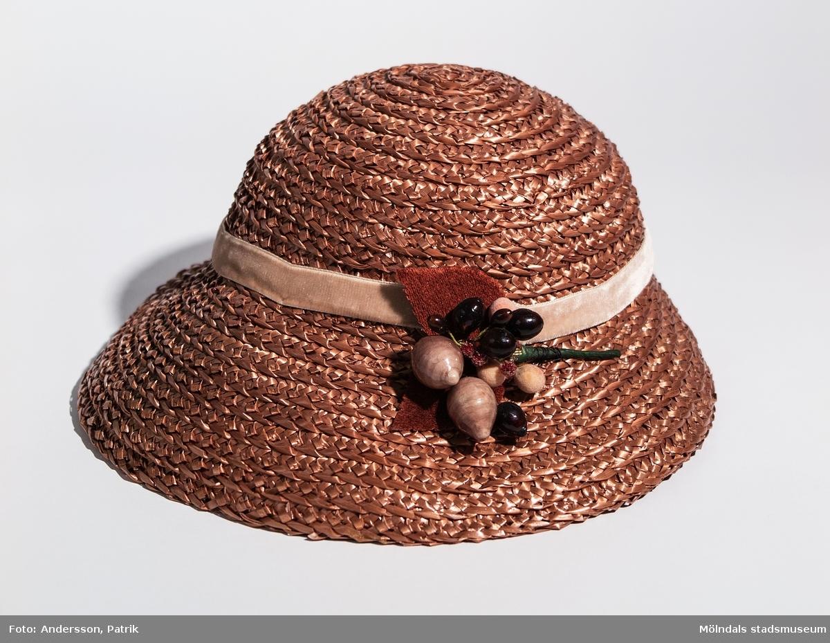 """Damhatt inköpt i Eskilstuna, troligtvis på 1930-talet. Hatten är ljusbrun och har ett ljusbrunt band runt kullen. Den har papier-maché dekoration fastsydd på vänster sida av hatten. I hatten finns en pappersetikett fastsydd där siffrorna   """"4551 4229 696"""" står skrivna med blyerts.  Enligt uppgift från givaren är hatten inköpt på 1920-talet, men eftersom butiken öppnade 1934 är hatten troligen inköpt på 30-talet."""