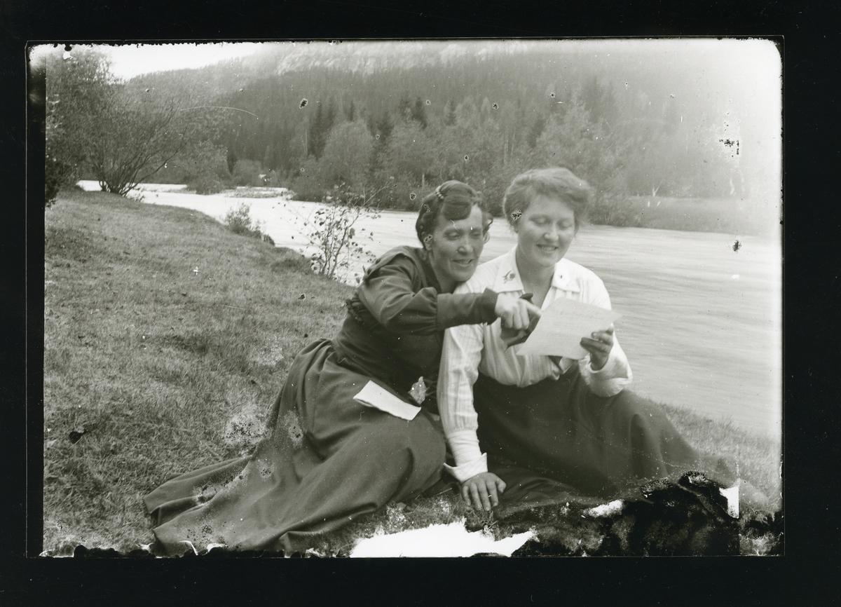 To kvinner sitter på graset ved ein elvebredd. Dei les eit brev.