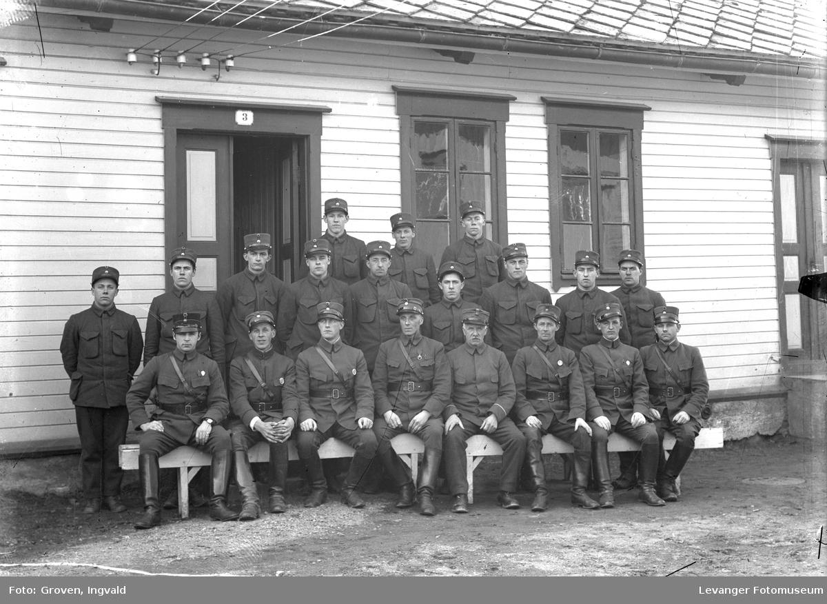 Soldater foran et t hus merket med talle tre, militærbrakke.