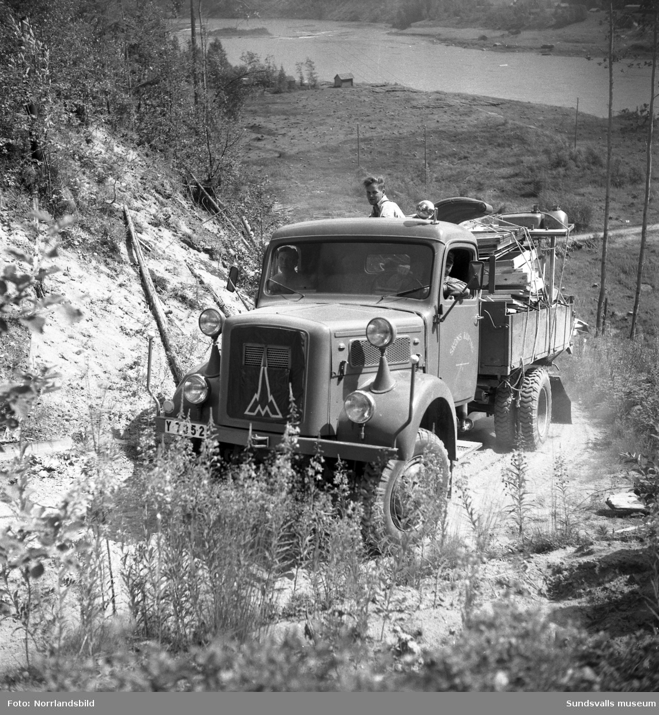 En lastbil körs uppför en brant grusväg invid en älv. Näslund & Burestad.