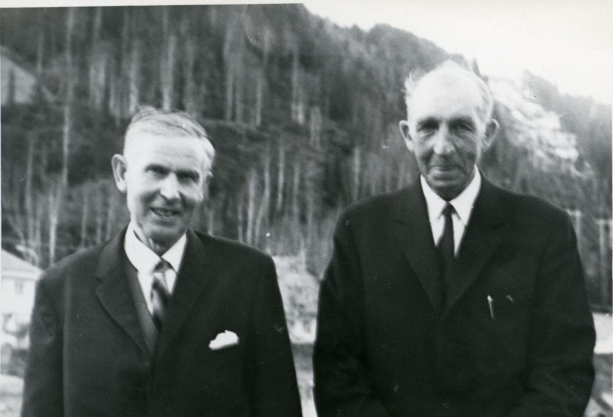 Portrett av 2 menn i halvfigur. Begge har mørk dress.