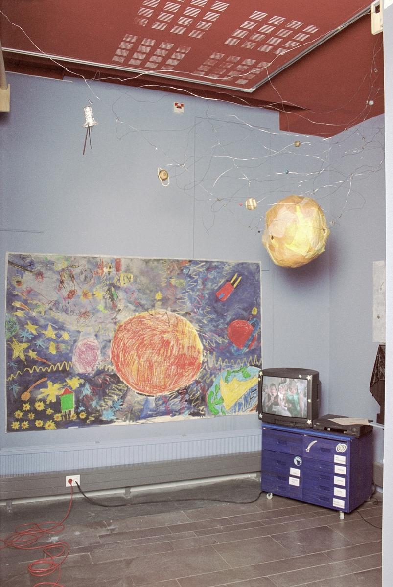 """Utställningen """"Solprojekt"""" 00-06-08 - 00-09-08 i Teknorama. Solsystemet i taket av elever från IMR. Aktivitetskåp av elever från IMR. Teckningar av elever från Schoolaris. TV med solkonsert?+animerad film av IMR och Schoolaris."""