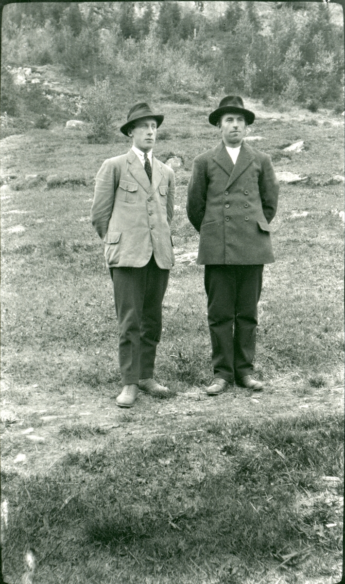 2 menn står på en sti i utmark. Begge har dressjakke, skjorte og slips.