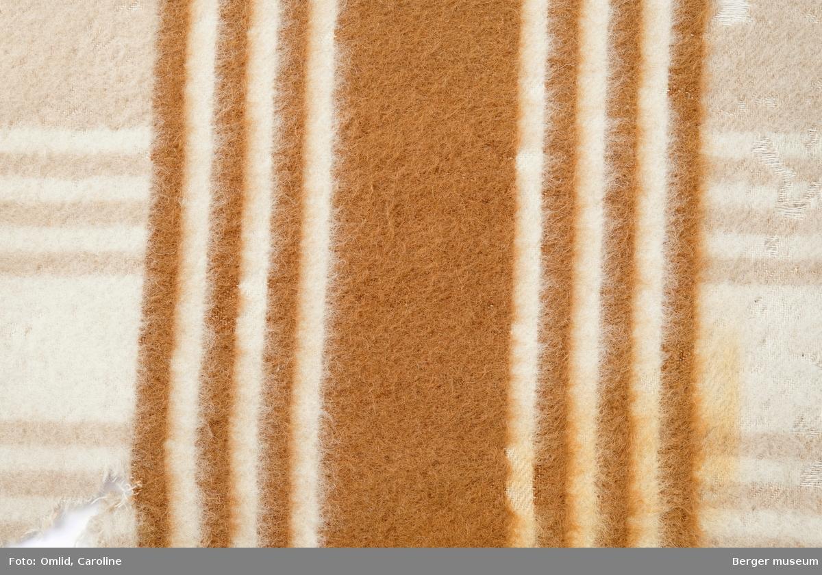 Teppeprøve med langsående stripemønster. Brede striper i annehver beige og off-white i teppet, et felt med  striper i rustrødt som tverrgående bord, tre smale striper på hver side av et bredt felt.  Behandling: Oppfukting med vann i sprayform. Vask i varmt vann tilsatt 1 tsk Berol 784. Innsåping med Marseille-såpe. Skylling i 3 hold varmt vann. Tørking på bord, med vifte, ca. 5 timer.