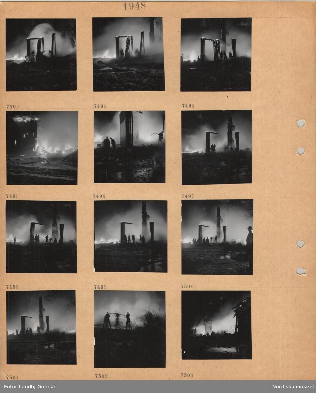 Motiv: Män som bekämpar elden vid brinnande hus i mörker.