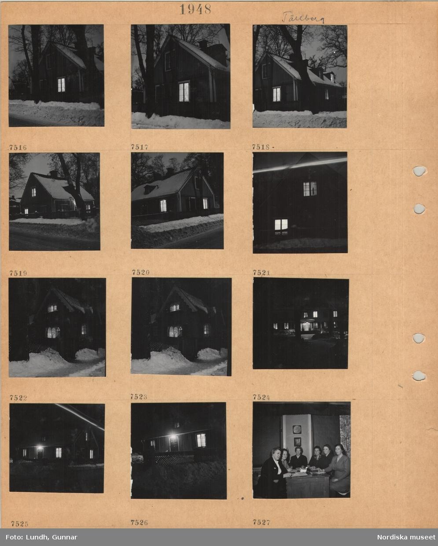 Motiv: Tällberg, bostadshus i snö, upplysta fönster, plogad väg, sex kvinnor sitter runt ett skrivbord med papper och penna, porträtt av Hjalmar Branting på väggen.