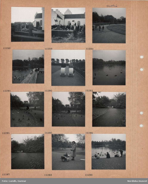 Motiv: Begravning vid Brunnby kyrka, kyrkogård, gravstenar, låga häckar, begravningsgäster vid graven, Malmö, park med gångväg, två flickor, gräsytor, häckar, en kvinna matar vildfåglar vid en damm, två kvinnor med barnvagn, stor damm med vilda fåglar, gräsänder och fiskmåsar på gräsyta, kvinna med barnvagn, pojke, gångväg mellan gräsytor, träd, person med barnvagn sitter på en bänk, kvinna i kappa och hatt med barn i sittvagn, barn matar gräsänder i stor damm.