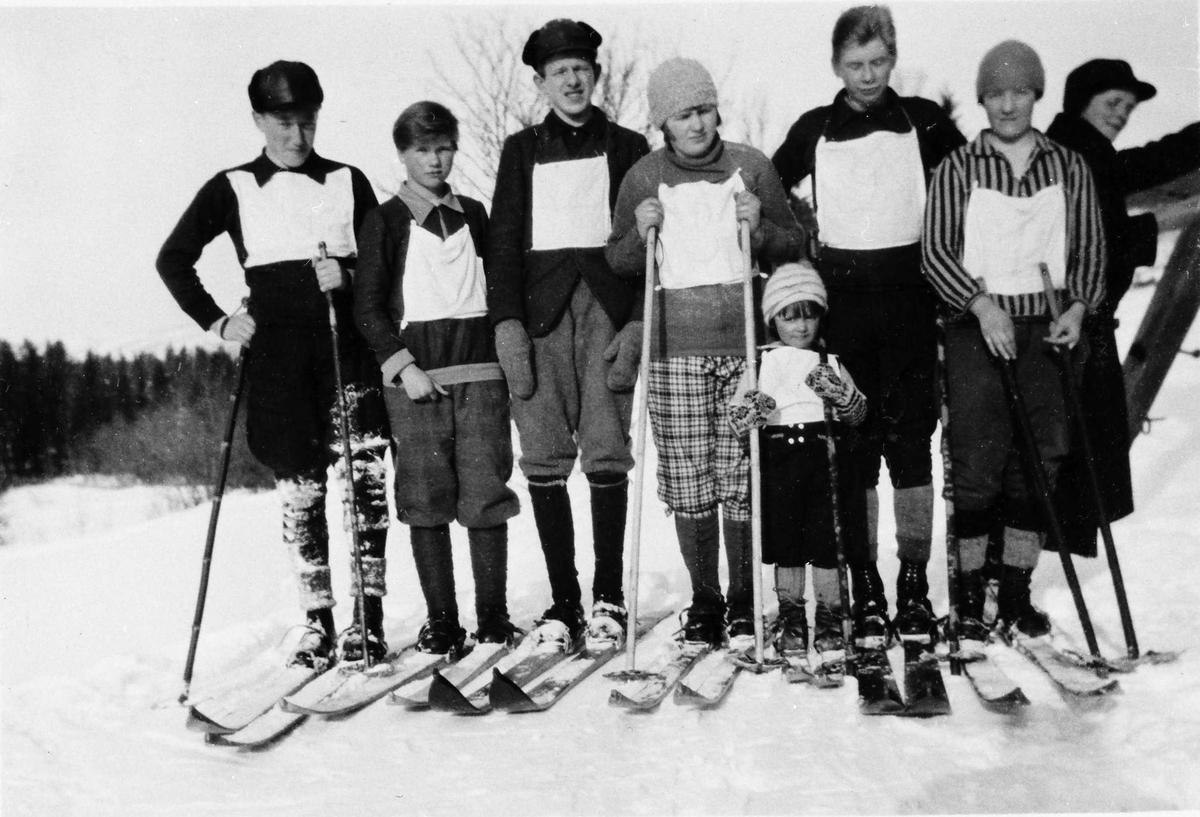Personer, klær, ski og skistaver.
