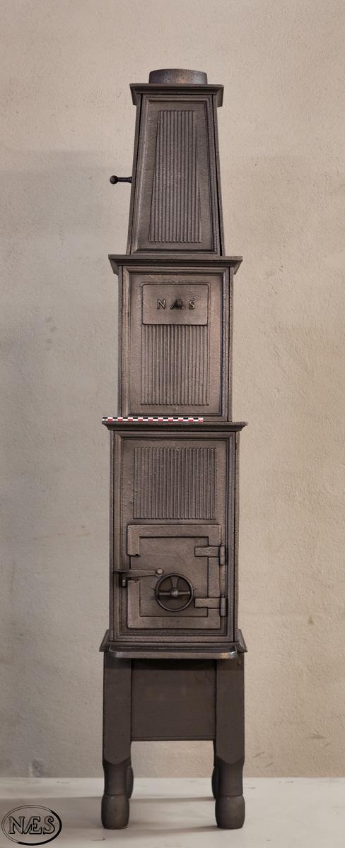 Ovn i to etasjer med pyramidetopp. Røkrør i toppen og ovnsluke på kortsiden. Lufteventiler på kortside 2. etg og langside 3.etg. Ovnsplatene har riflet bunn. På langside 1. etg er en oval stående medaljong hvor en kvinne med draperier holder en krans i sin høyre hånd. 2. etg er det en gjennomgående sirkelformet åpning med en gjennombrutt blomst i den ene enden. Pyramidetoppen har en rosett på hver langside.