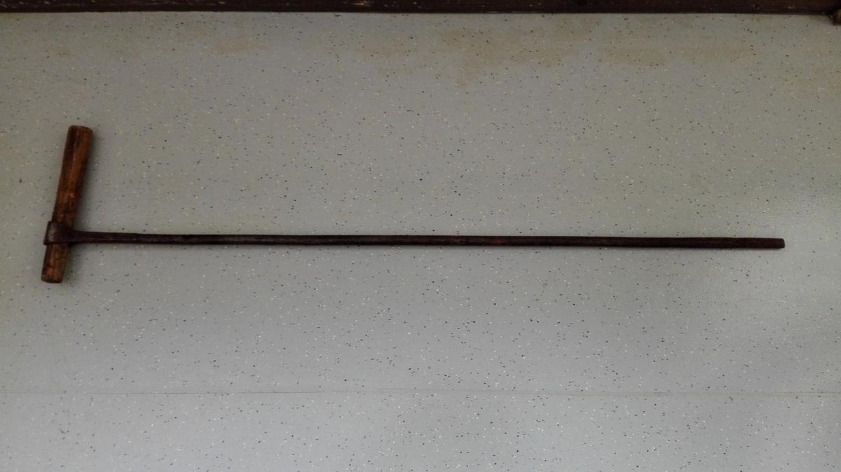 Defekt navar med laust rundt trehandtak som er stukke inn i ein bøyle (hol) på toppen av navaren. Handtaket er ikkje sentrert, og navaren har truleg vore skrudd  med berre ei hand.  Borspissen manglar.