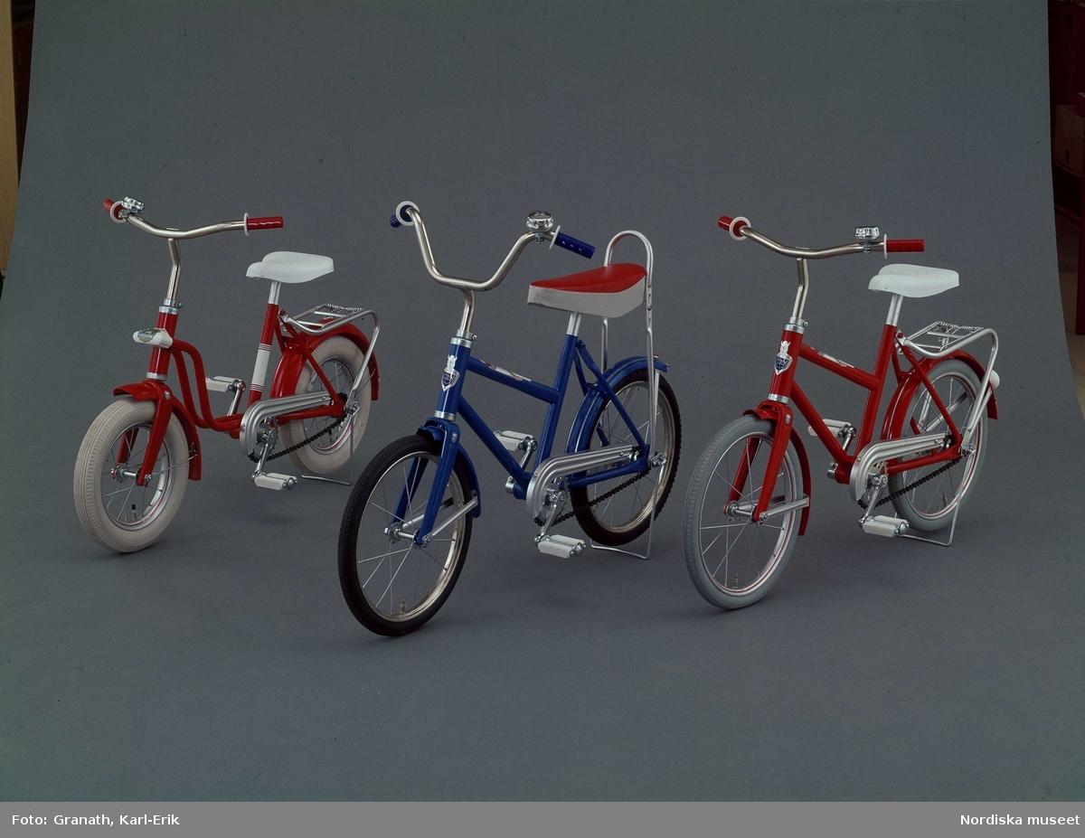 Tre olika modeller av barncyklar. Obeskuret produktfoto i studio mot grå fond.