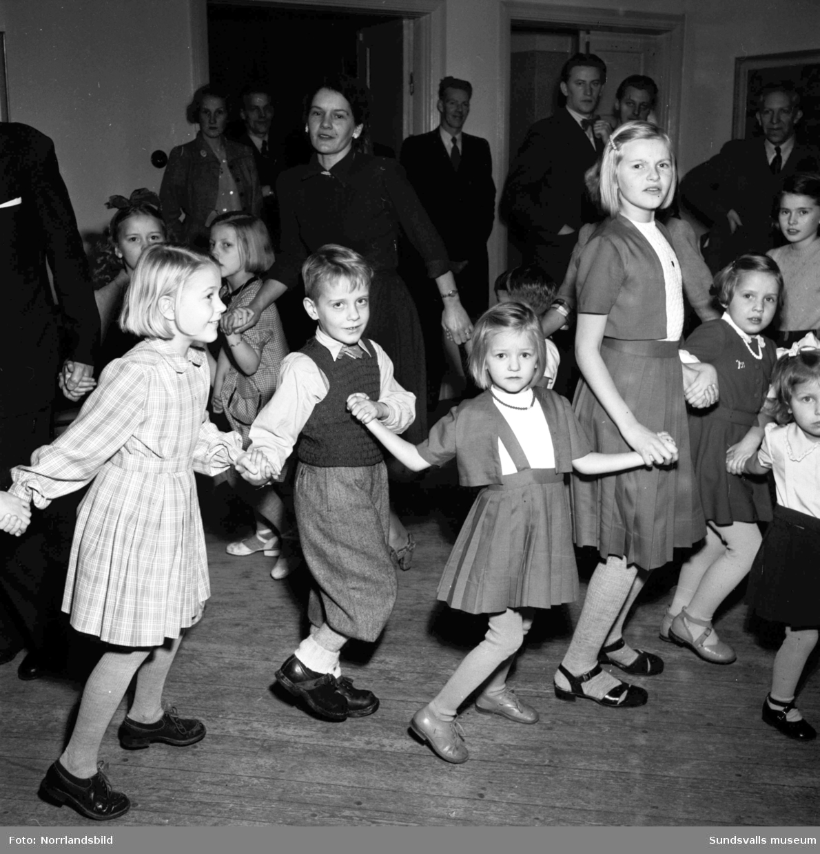 Barnjulfest, julgransplundring, i Sundsvalls Folkets hus. En liten flicka spelar dragspel och långdans med glada barn.