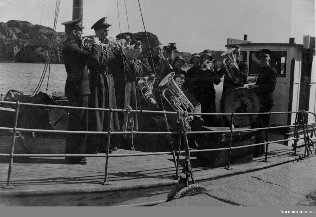 Stabsmusikkorpset, står det på tromma. Korps fra Frelsesarmeen, med ei dame på trompet, ombordf på en båt. Uniformer. Tuba,. althorn, baryton, basun. Hvor er de på tur til? Nordmøre museums fotosamling.