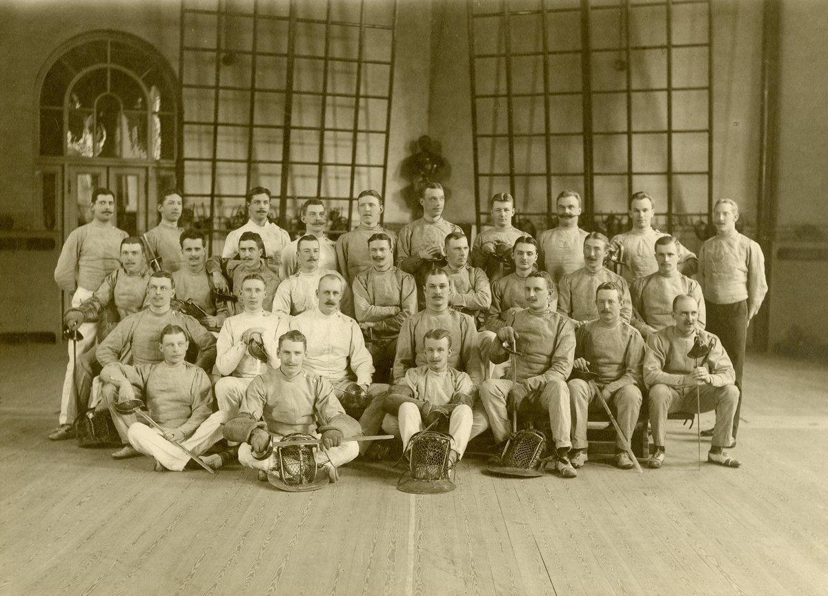 Grupporträtt av fäktare i gymnastiksal, omkring 1900.