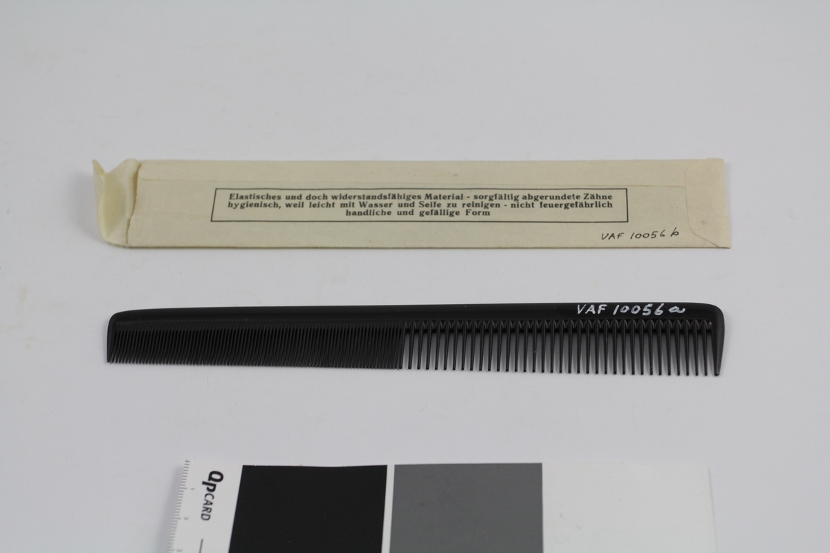 Kam (a) i original papirpose (b). Den ene halvparten fintannet, den andre grovere. Smalner litt mot den fintannede delen. Papirpose av ett stykke papir, med trykket tekst (se foto), åpning i den ene kortsiden.