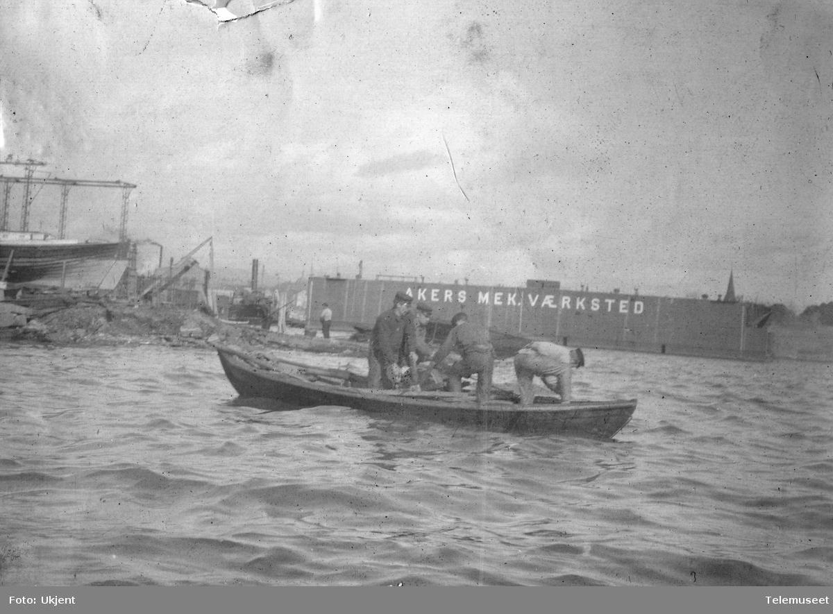Robåt med fire personer utenfor Flytedokken til Akers mekaniske værksted,  Kristianiafjorden