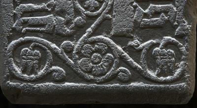 Detalj fra en middelaldergravstein; en flott uthugget fembladet blomst med bladranker rundt.