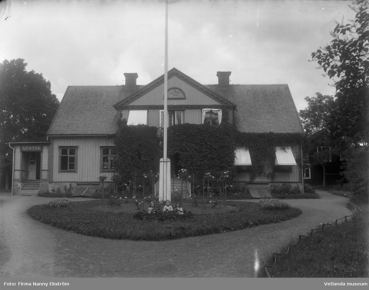 Apoteket i Vetlanda. Tre barn sitter framför flaggstången.