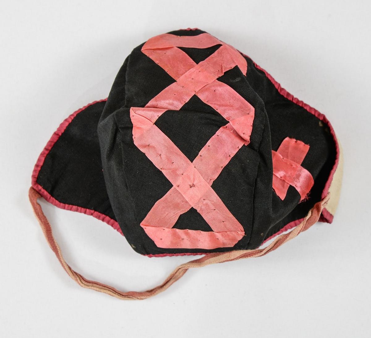 Dåpslue i svart silke, pynta med rosa silkeband i kors og anna mønster. Kanta rundt helile lua med rosa silke.  Fóra med bomull. Eitt vevd knyteband i rosa og beige.