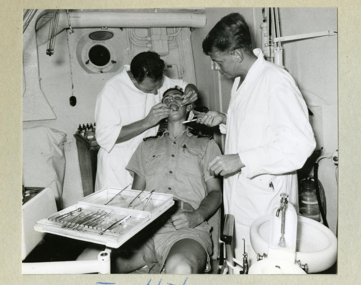 Bilden föreställer en besättningsmedlem som blir undersökt av tandläkare i vita rockar ombord på minfartyget Älvsnabben. Bilden är tagen under långresan 1966-1967.