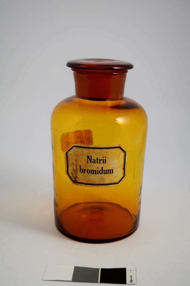 Brun glasskrukke med vid hals og brun glasspropp. Påført to hvite etiketter med sort skrift. Krukken ble brukt til oppbevaring av pulver. Natriumbromid ble brukt som beroligende middel.