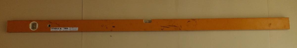 Lang rektangulær bygningsvater i aluminium. Tre sider er lakkert oransje, medan undersida er blank. To dropeglas, eitt for horisontal måling og eitt for vertikal måling.