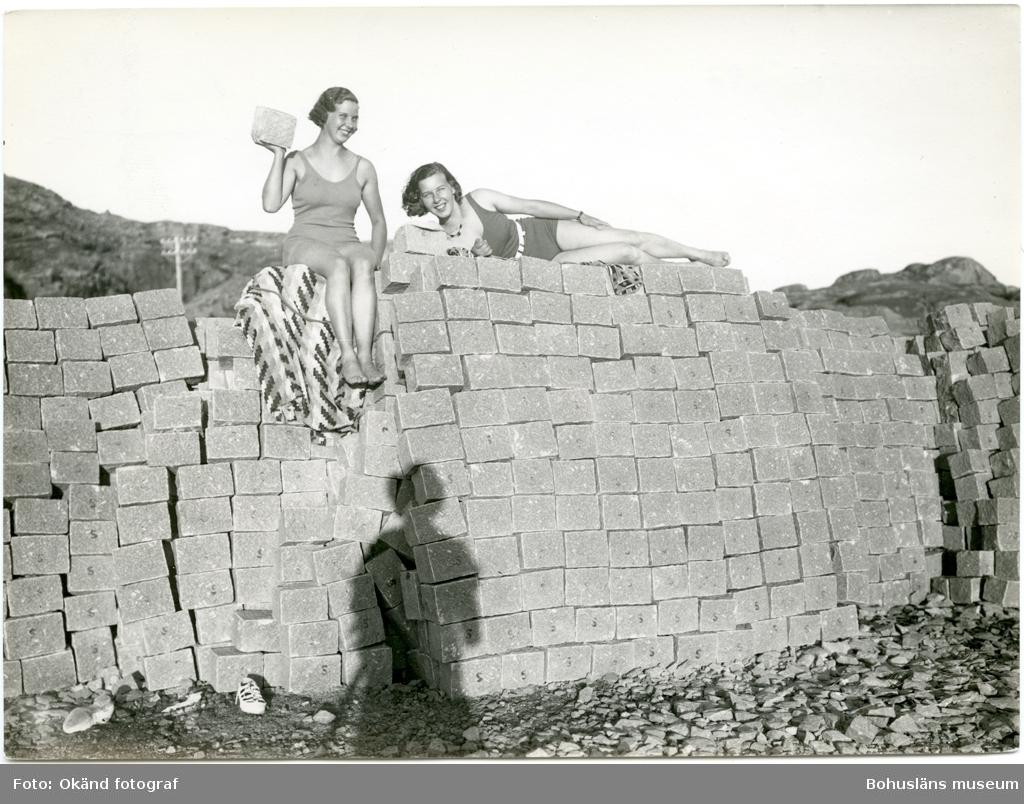 Två kvinnor sitter repsektive ligger på en stapel med gatsten och solbadar, den ena håller en gatsten i sin ena hand, fotografens skugga syns i nedre delen av bilden