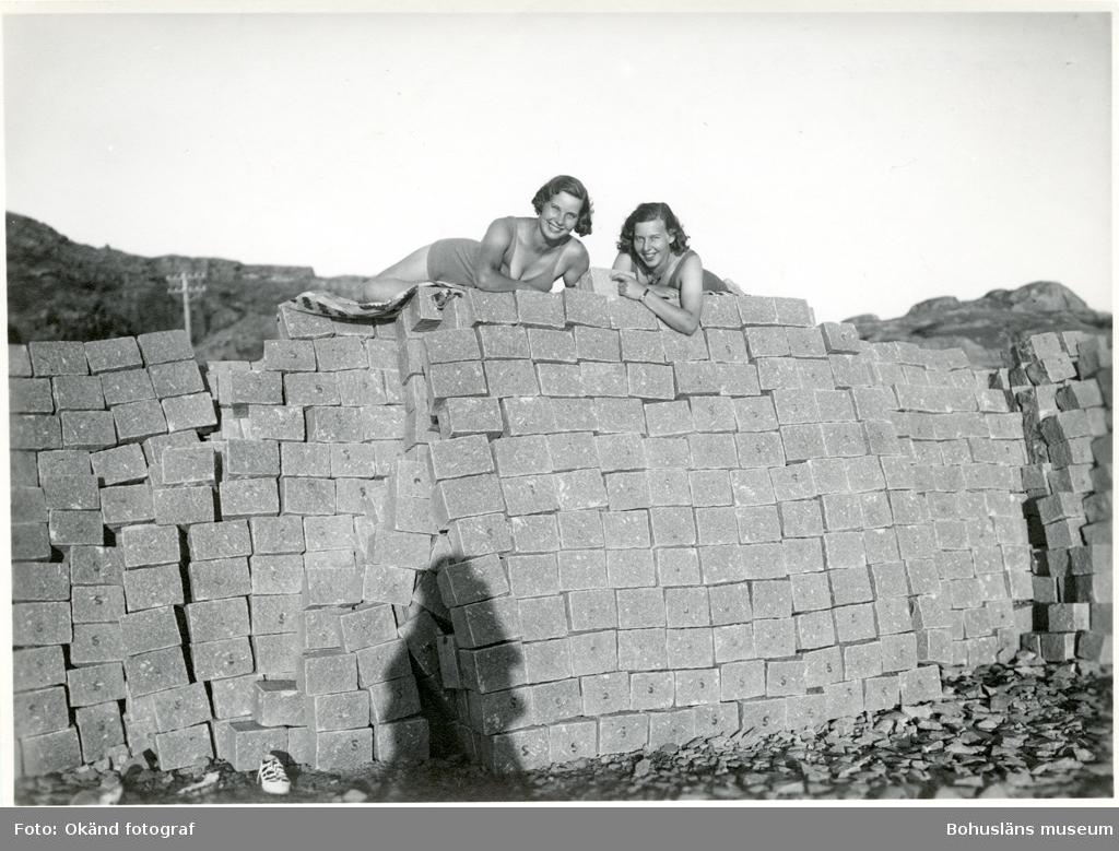 Två kvinnor ligger på en stapel med gatsten, fotografens skugga syns i bildens nederkant