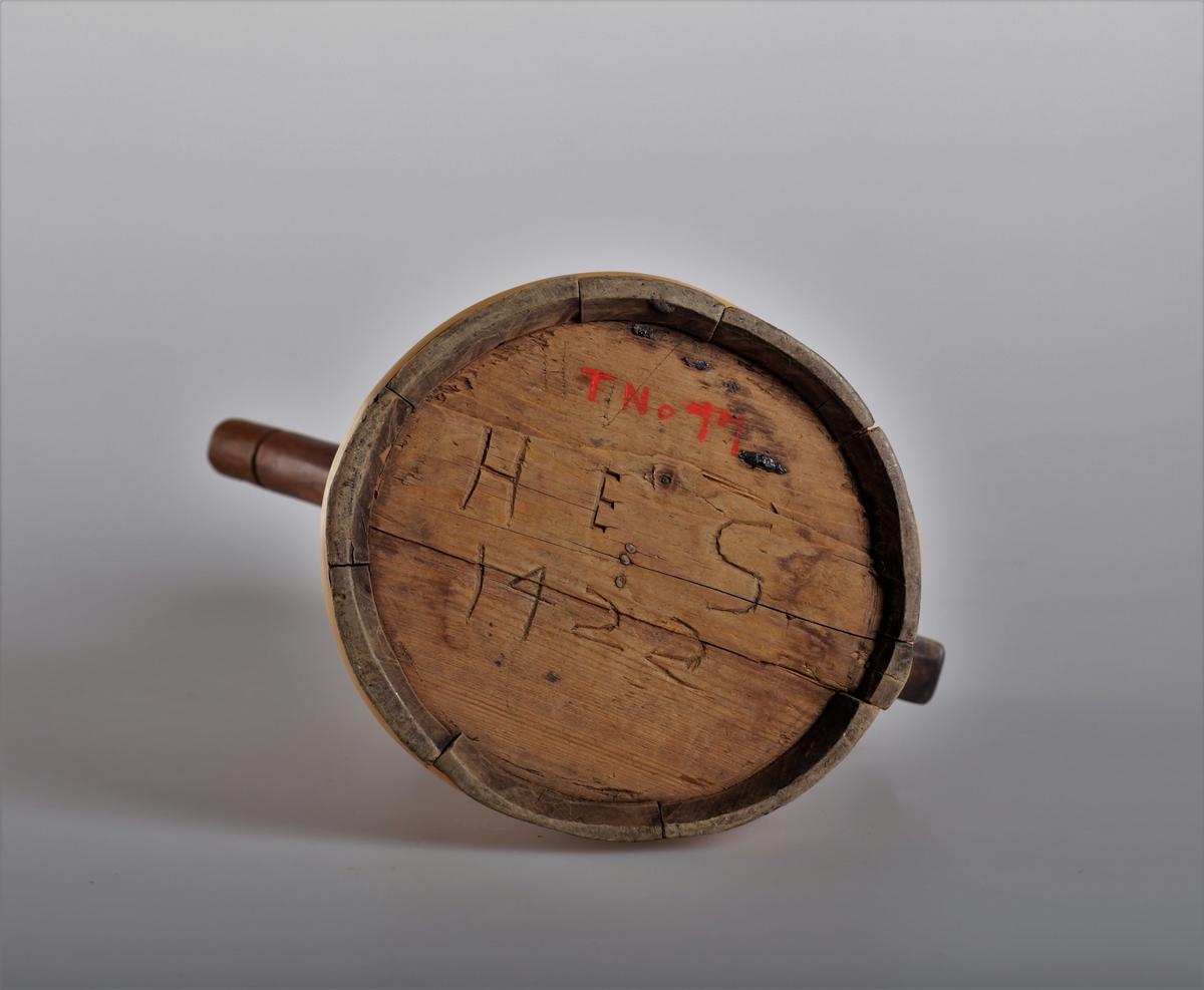 Kanna har tut og er lagget. Trebandene som er sveipet rundt beholderen har en annen patina enn stavene, og der virker derfor som om kannen er reparert i nyere tid. Kannen har innsvidde ornamenter.