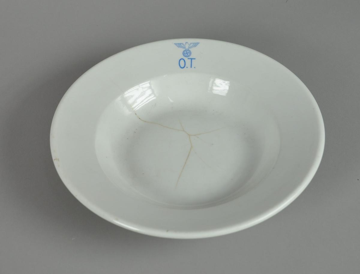 Dyptallerken av glassert keramikk. Keramikken har noen sprekker, og på oversiden av tallerkenen er det et blått stempel med nazistisk emblem.