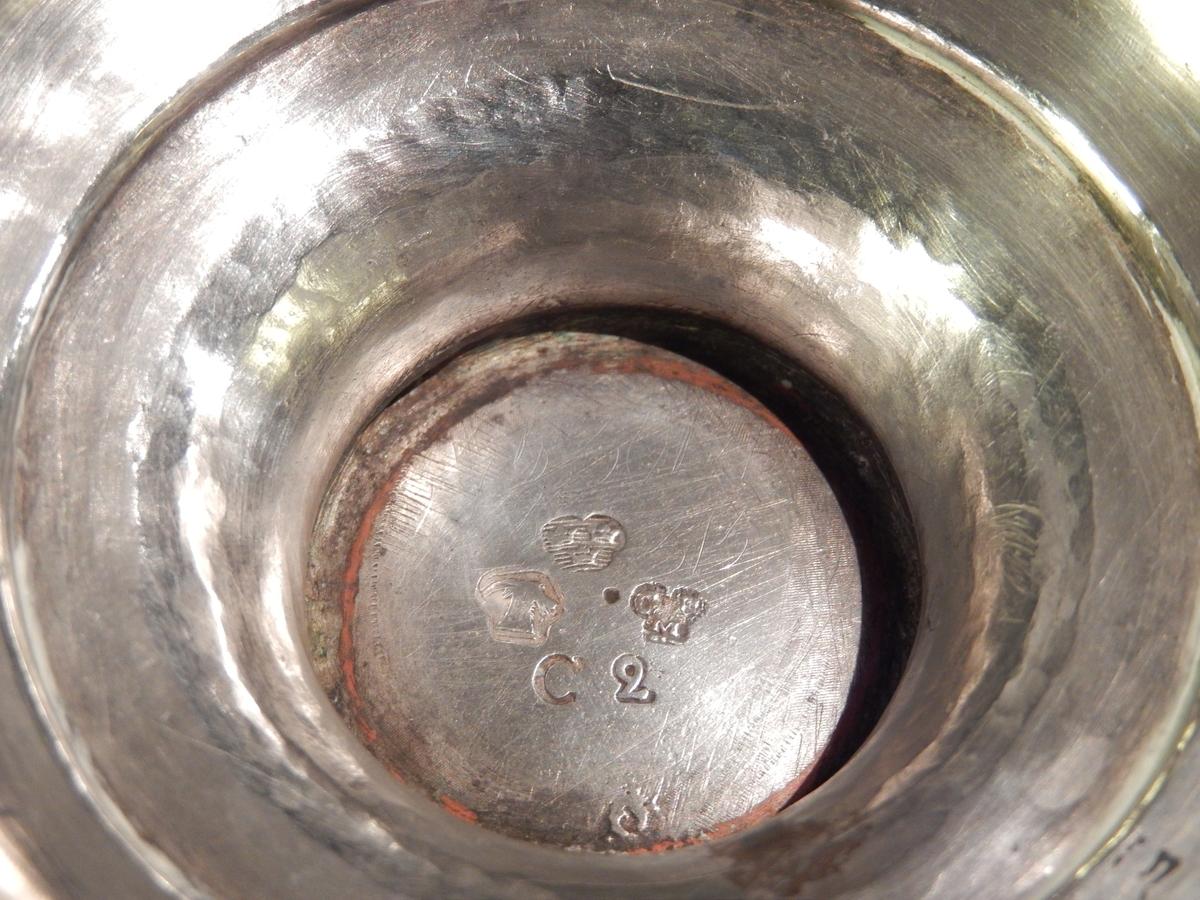 Skål i silver, delvis förgylld, med rikt graverad ornamentik på buken. Skålens brätte är svagt utvikt och förgyllt. På buken, rikt graverad dekor i form av bladranka på övre delen, strax därunder fyra sköldar med lövverk vid sidan och ett blad i mitten. I ena skölden bokstäverna H.I.S.A.N.D. samt monogrammet AD. På nedre delen av buken är bokstäverna JHS och HKID graverade. De två hänklarna är förgyllda och i form av en drake. Drakens vingar är på utsidan rikt graverade. Hänklarna är gjutna. Skålens fot är skålformad och förgylld. Stämplar i botten.